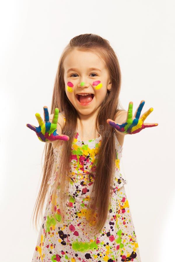 Το μικρό κορίτσι με τα χέρια χρωμάτισε στο ζωηρόχρωμο χρώμα στοκ εικόνες