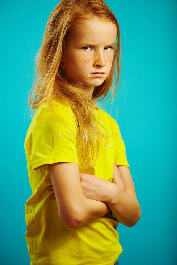 Το μικρό κορίτσι με τα όπλα που διασχίζονται στο στήθος, 0 ή αγανακτισμένος, εκφράζει μια κακή και λυπημένη διάθεση στοκ φωτογραφία