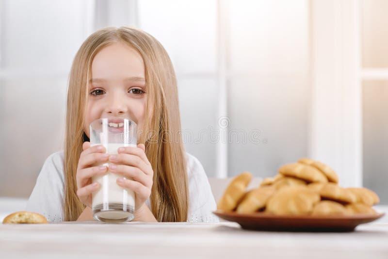 Το μικρό κορίτσι με την ξανθή τρίχα κρατά το γυαλί με το γάλα στοκ εικόνες