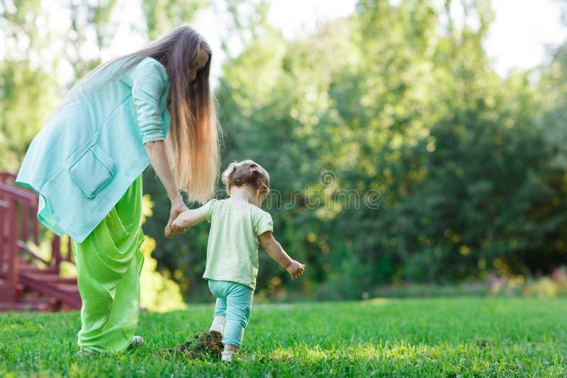 Το μικρό κορίτσι με τη μητέρα πηγαίνει στο χορτοτάπητα στοκ εικόνες