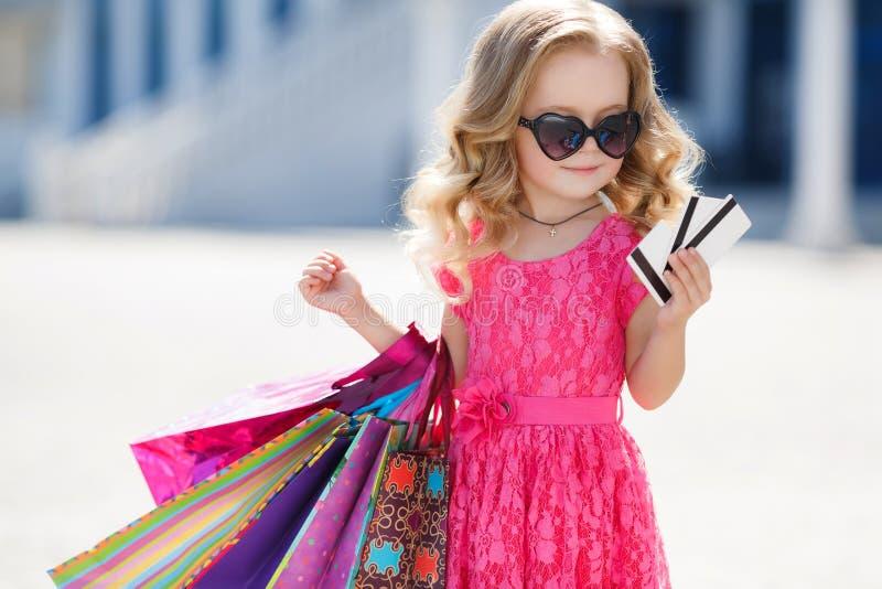 Το μικρό κορίτσι με τις τσάντες αγορών πηγαίνει στο κατάστημα στοκ φωτογραφίες