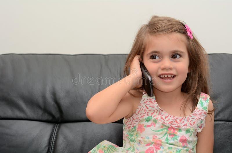 Το μικρό κορίτσι μιλά στο τηλέφωνο στοκ φωτογραφία
