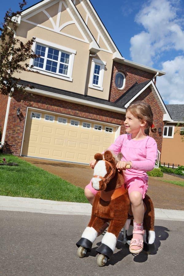 Το μικρό κορίτσι οδηγά στο άλογο παιχνιδιών κοντά στο εξοχικό σπίτι στοκ εικόνες με δικαίωμα ελεύθερης χρήσης