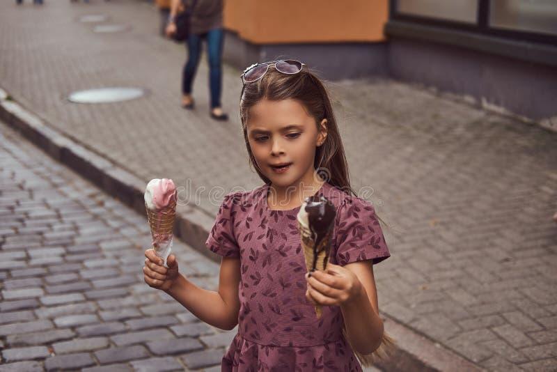 Το μικρό κορίτσι ομορφιάς σε ένα μοντέρνο φόρεμα κρατά δύο κώνους παγωτού, που στέκονται στην οδό θερινών πόλεων στοκ εικόνα