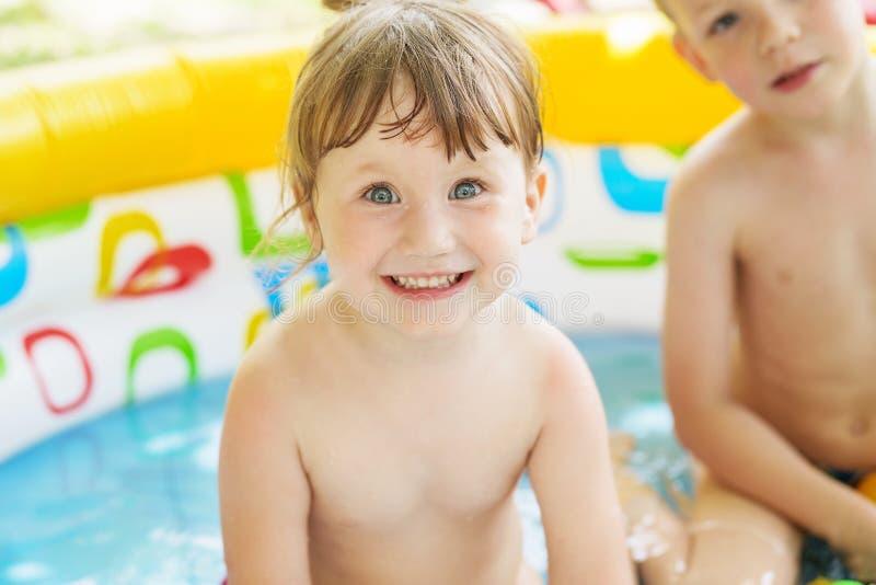 Το μικρό κορίτσι λούζει στην κίτρινη διογκώσιμη κολυμπώντας κωπηλατώντας λίμνη ο στοκ φωτογραφίες με δικαίωμα ελεύθερης χρήσης