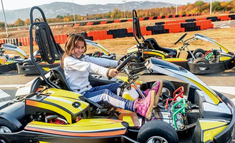 Το μικρό κορίτσι οδηγεί πηγαίνει αυτοκίνητο Kart σε μια διαδρομή αγώνα παιδικών χαρών στοκ εικόνες