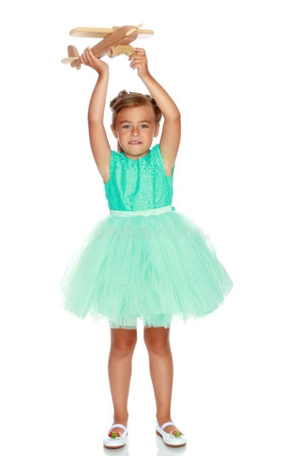 Το μικρό κορίτσι παίζει με ένα αεροπλάνο στοκ φωτογραφία