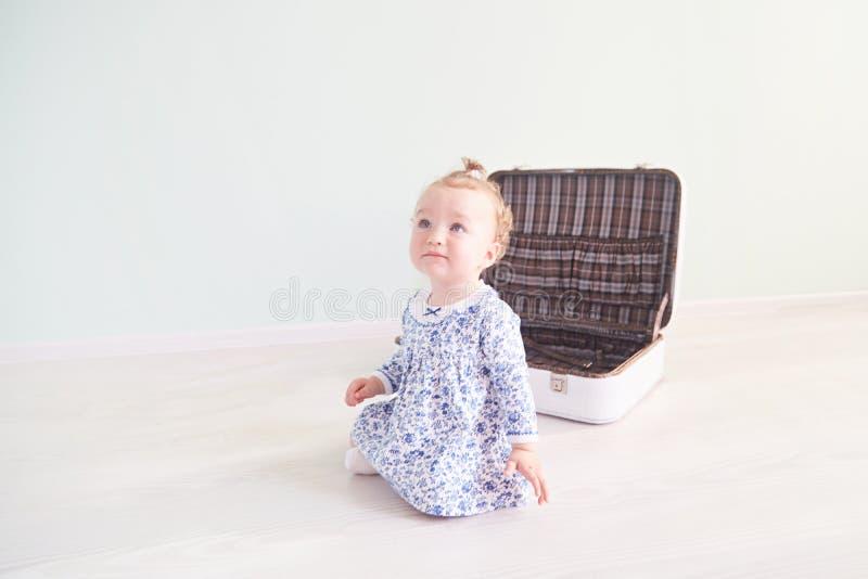 Το μικρό κορίτσι παίζει με μια άσπρη βαλίτσα στοκ εικόνες με δικαίωμα ελεύθερης χρήσης