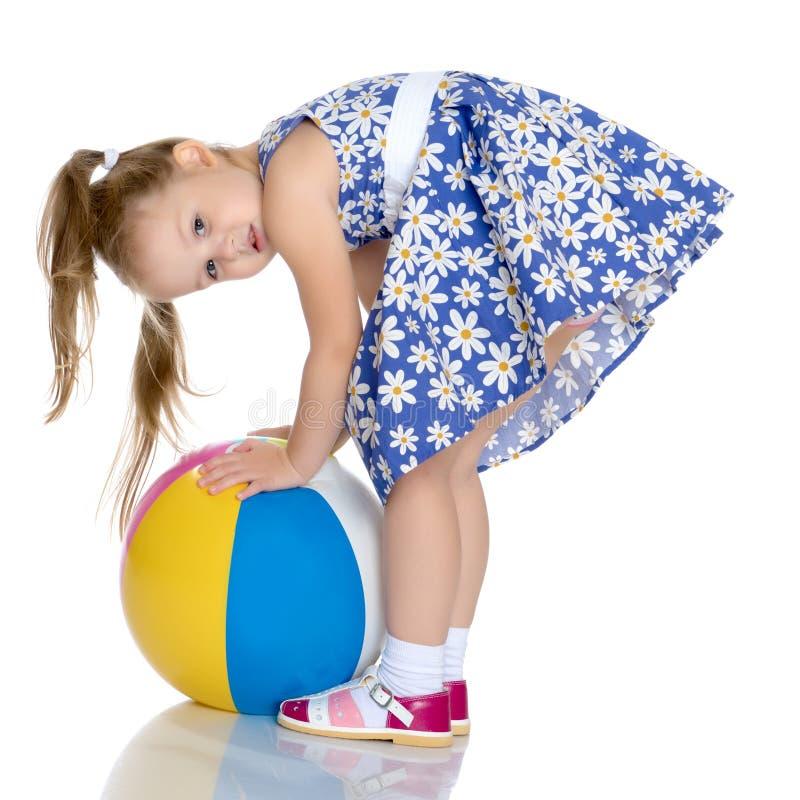 Το μικρό κορίτσι παίζει με μια σφαίρα στοκ εικόνα