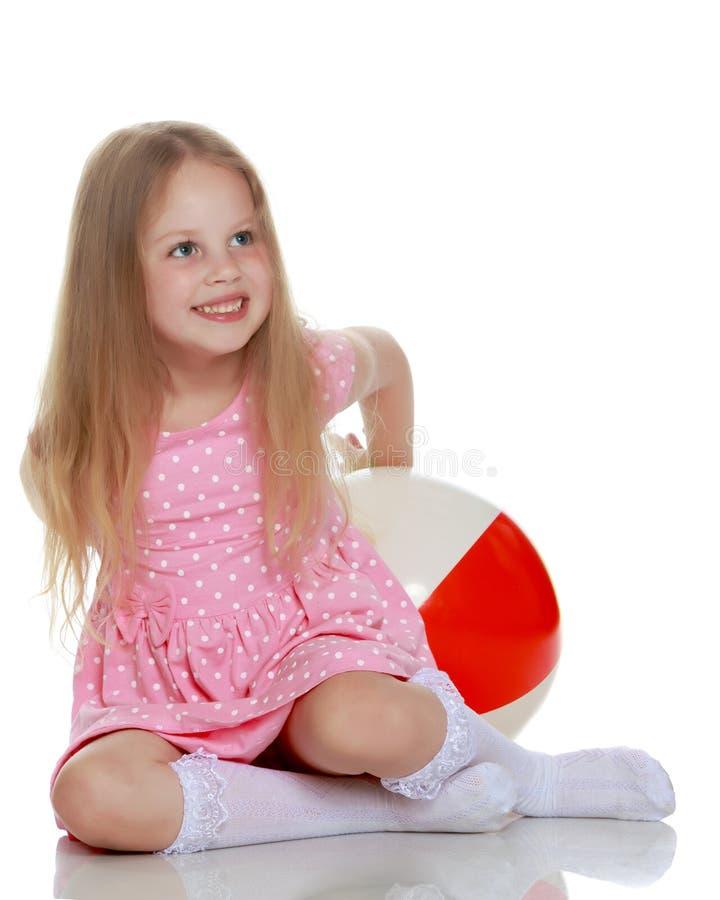 Το μικρό κορίτσι παίζει με μια σφαίρα στοκ φωτογραφία