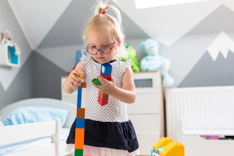 Το μικρό κορίτσι παίζει με τους φραγμούς στο δωμάτιό της στοκ φωτογραφία