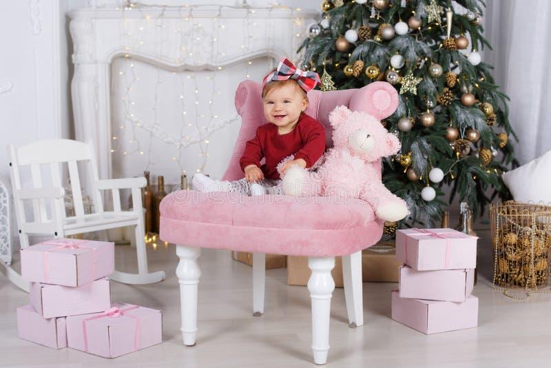 Το μικρό κορίτσι παίζει μόνο ενάντια σε ένα όμορφο χριστουγεννιάτικο δέντρο στη Παραμονή Χριστουγέννων στοκ εικόνες