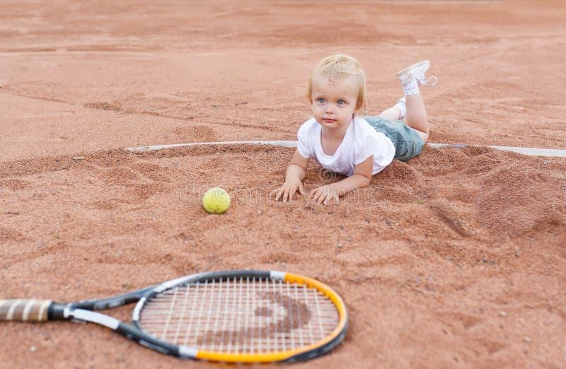 Το μικρό κορίτσι που βρίσκεται στο γήπεδο αντισφαίρισης Μικρό κορίτσι, σφαίρα αντισφαίρισης και ρακέτα στοκ εικόνες με δικαίωμα ελεύθερης χρήσης