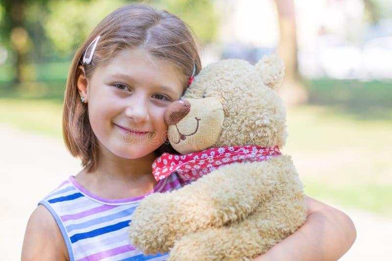 Το μικρό κορίτσι που κρατά μεγάλο teddy αντέχει έξω στοκ φωτογραφίες