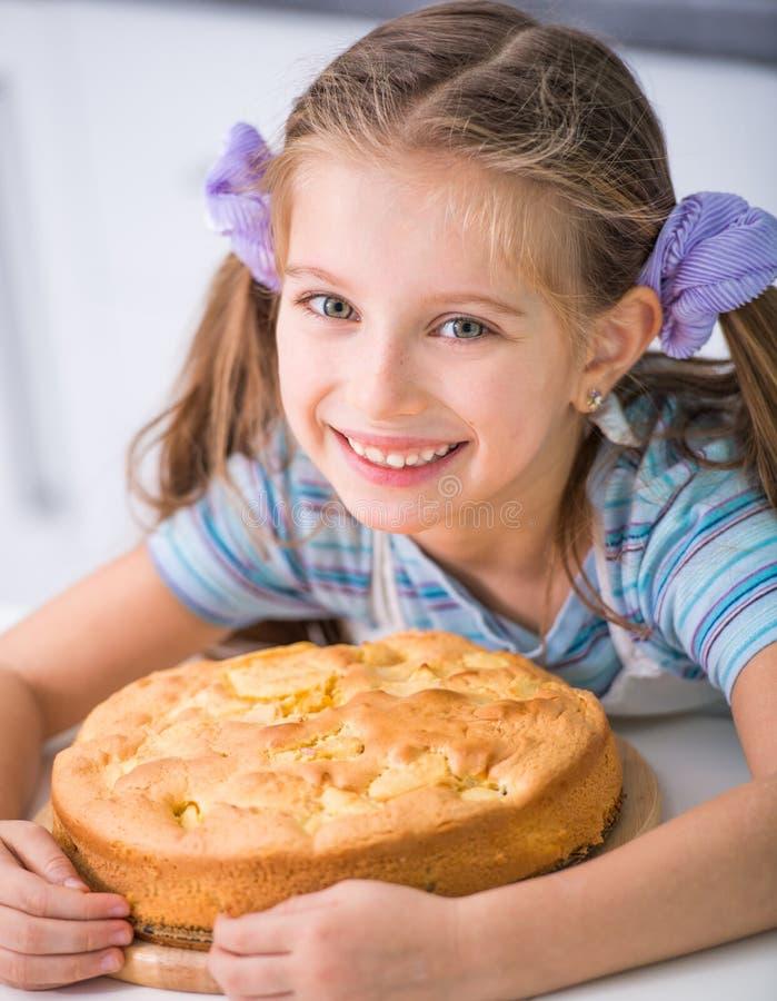 Το μικρό κορίτσι προετοιμάζει μια πίτα μήλων στοκ εικόνες