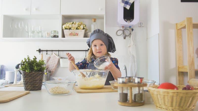 Το μικρό κορίτσι προσθέτει oatmeal στη ζύμη ζύμης στοκ φωτογραφία
