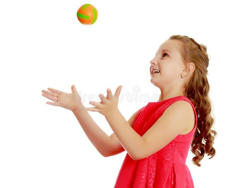 Το μικρό κορίτσι ρίχνει τη σφαίρα επάνω στοκ φωτογραφία