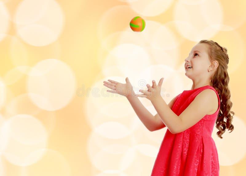 Το μικρό κορίτσι ρίχνει τη σφαίρα επάνω στοκ εικόνες με δικαίωμα ελεύθερης χρήσης