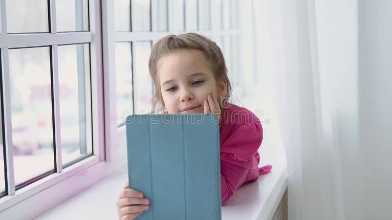 Το μικρό κορίτσι σε ένα ρόδινο φόρεμα κάθεται από το παράθυρο με μια ταμπλέτα στοκ φωτογραφία