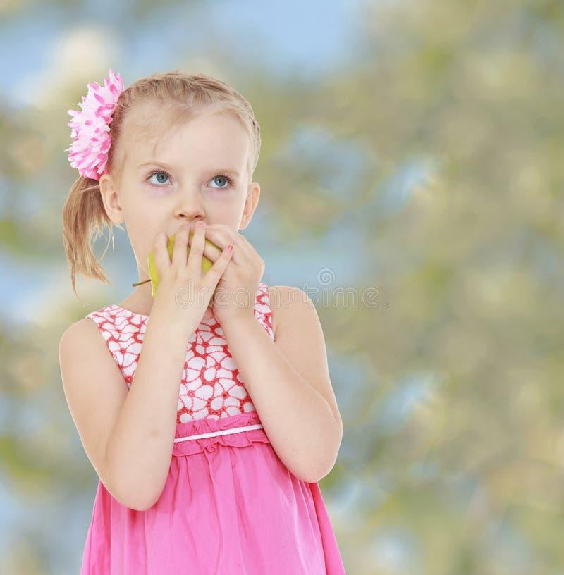 Το μικρό κορίτσι σε ένα ρόδινο φόρεμα δαγκώνει τη Apple, χλωμή στοκ εικόνα με δικαίωμα ελεύθερης χρήσης