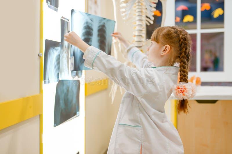 Το μικρό κορίτσι σε ομοιόμορφο εξετάζει την ακτίνα X, γιατρός στοκ εικόνα με δικαίωμα ελεύθερης χρήσης