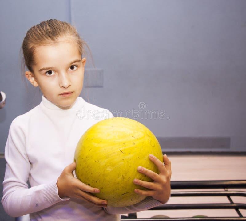 Το μικρό κορίτσι στέκεται και κρατά τη σφαίρα στη λέσχη μπόουλινγκ στοκ φωτογραφίες με δικαίωμα ελεύθερης χρήσης