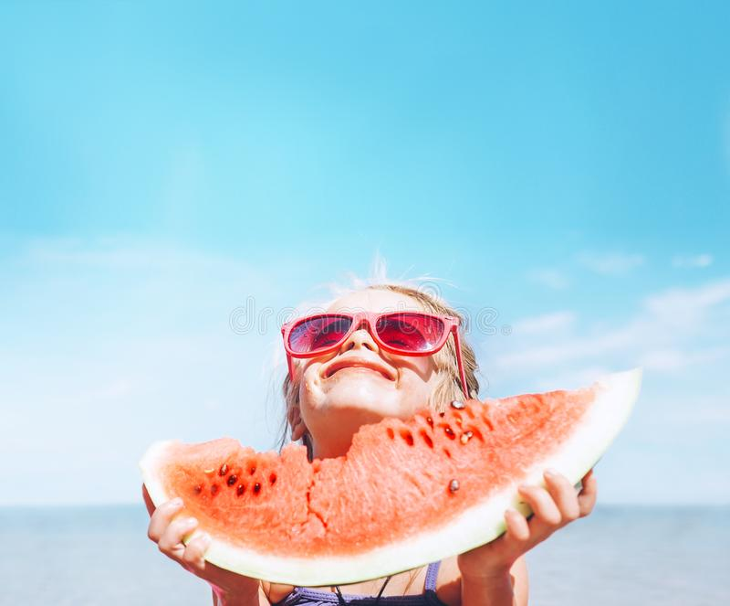 Το μικρό κορίτσι στα ρόδινα γυαλιά ηλίου με το μεγάλο καρπούζι τέμνει το αστείο πορτρέτο Υγιής εικόνα έννοιας κατανάλωσης στοκ φωτογραφία με δικαίωμα ελεύθερης χρήσης