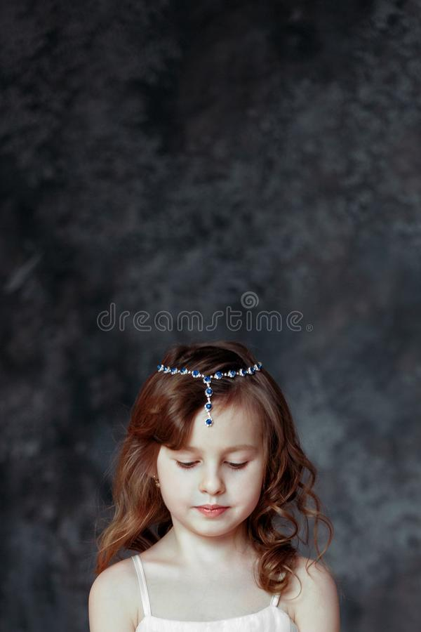 Το μικρό κορίτσι στο άσπρο φόρεμα στο δωμάτιο προσεύχεται στοκ φωτογραφία με δικαίωμα ελεύθερης χρήσης