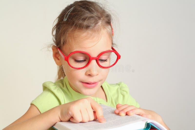 Το μικρό κορίτσι στο γυαλί έβαλε το δάχτυλο στο κείμενο στοκ εικόνα με δικαίωμα ελεύθερης χρήσης