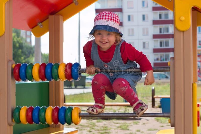 Το μικρό κορίτσι στο καπέλο αναρριχείται στην παιδική χαρά παιδιών σε ηλιόλουστο στοκ φωτογραφίες