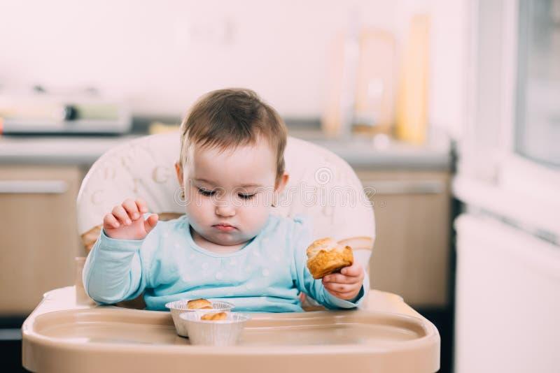 Το μικρό κορίτσι στο highchair στα χέρια Krapina, όπως muffins και croissants στοκ εικόνα
