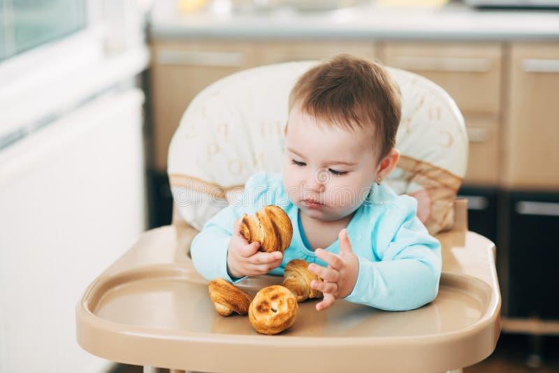 Το μικρό κορίτσι στο highchair στα χέρια Krapina, όπως muffins και croissants στοκ φωτογραφίες