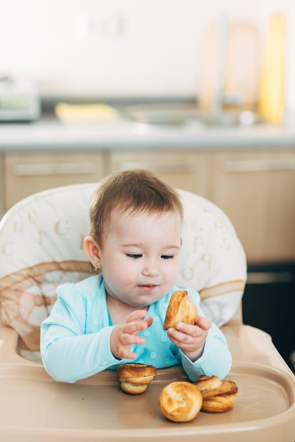 Το μικρό κορίτσι στο highchair στα χέρια Krapina, όπως muffins και croissants στοκ εικόνες