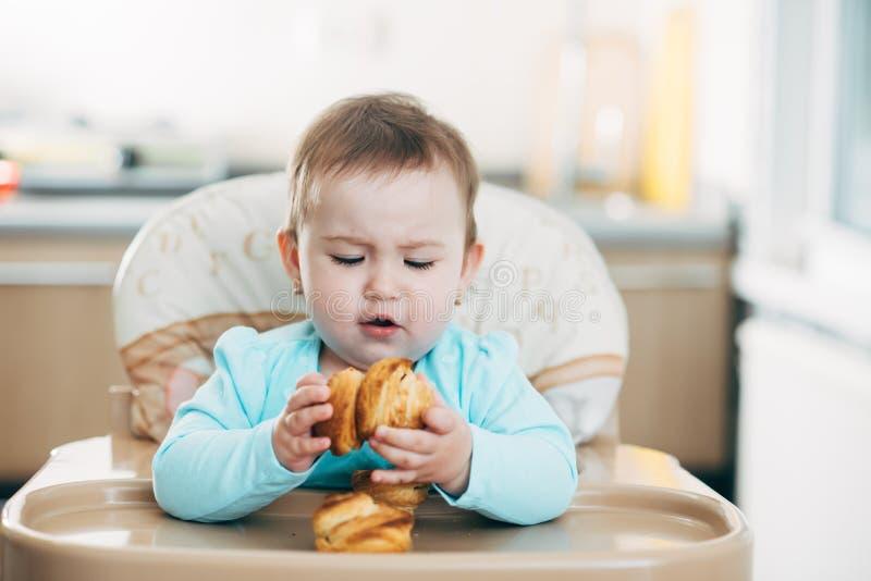 Το μικρό κορίτσι στο highchair στα χέρια Krapina, όπως muffins και croissants στοκ εικόνες με δικαίωμα ελεύθερης χρήσης