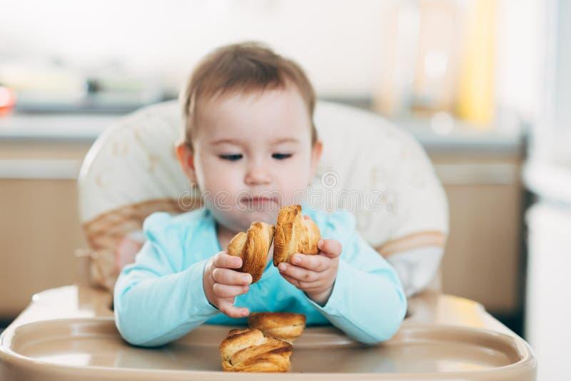Το μικρό κορίτσι στο highchair στα χέρια Krapina, όπως muffins και croissants στοκ φωτογραφία