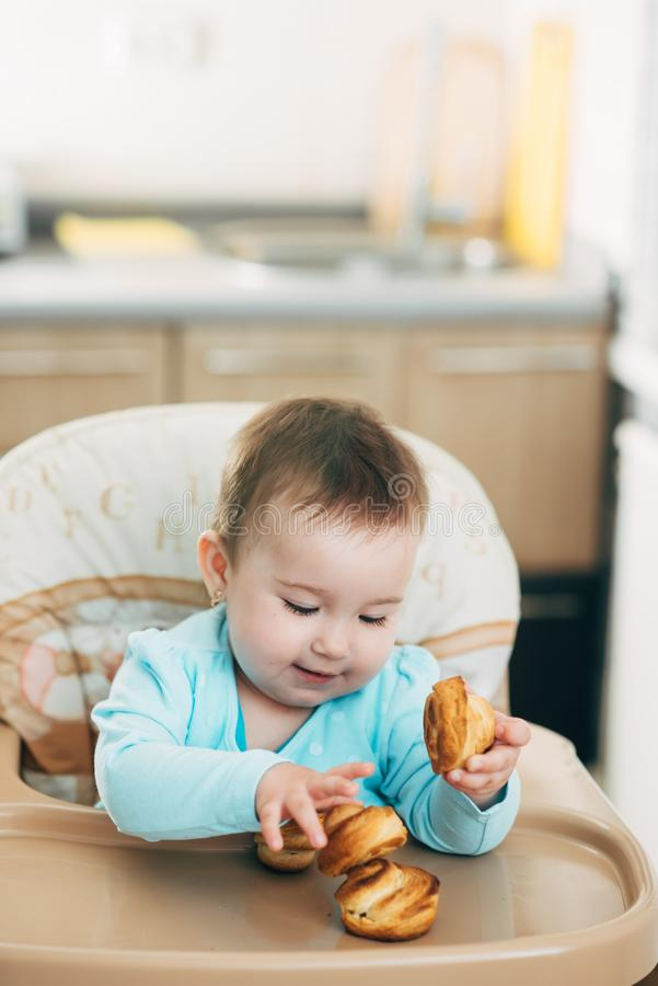 Το μικρό κορίτσι στο highchair στα χέρια Krapina, όπως muffins και croissants στοκ φωτογραφία με δικαίωμα ελεύθερης χρήσης