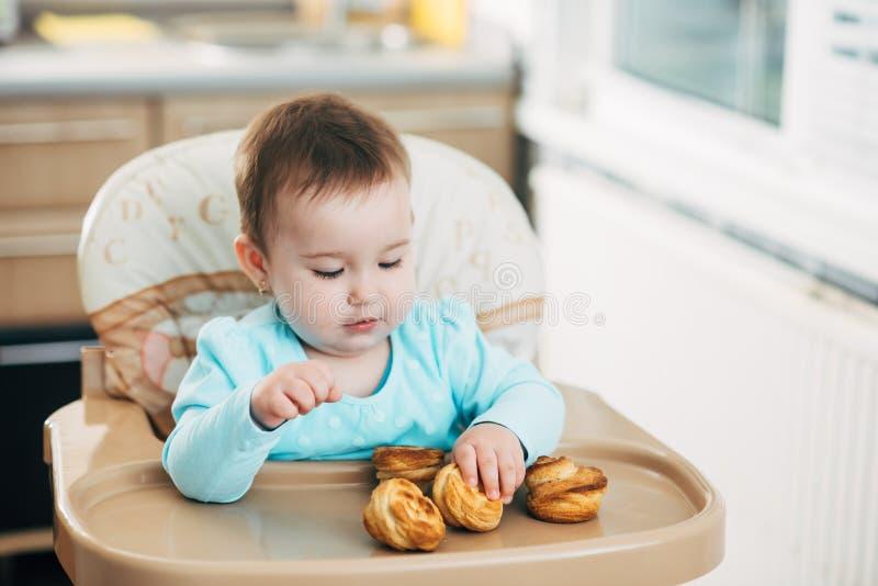 Το μικρό κορίτσι στο highchair στα χέρια Krapina, όπως muffins και croissants στοκ εικόνα με δικαίωμα ελεύθερης χρήσης