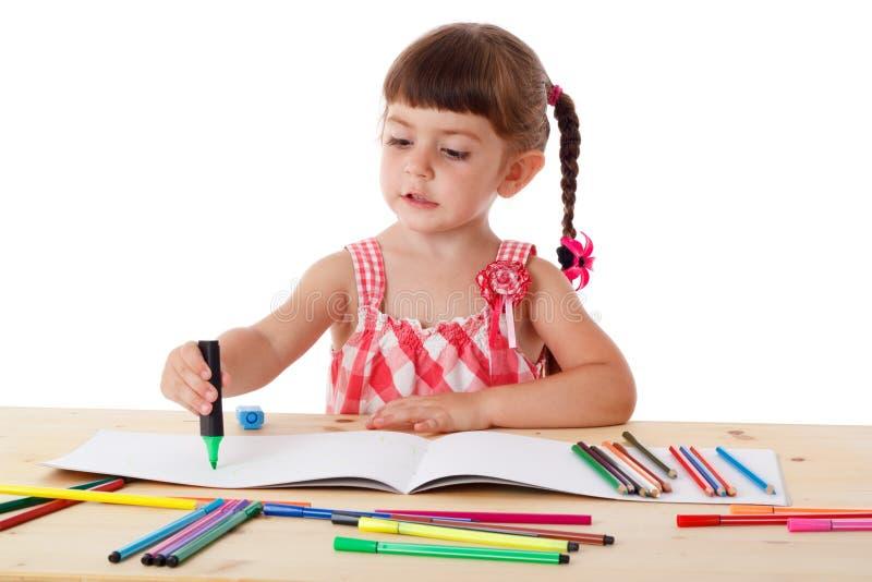 Το μικρό κορίτσι σύρει με τα κραγιόνια στοκ φωτογραφίες