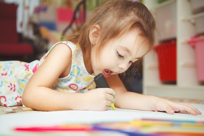 Το μικρό κορίτσι σύρει προσεκτικά την εικόνα στο σημειωματάριο με την αισθητή μάνδρα στοκ φωτογραφίες με δικαίωμα ελεύθερης χρήσης