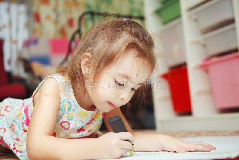 Το μικρό κορίτσι σύρει προσεκτικά την εικόνα στο σημειωματάριο με την αισθητή μάνδρα στοκ εικόνες με δικαίωμα ελεύθερης χρήσης
