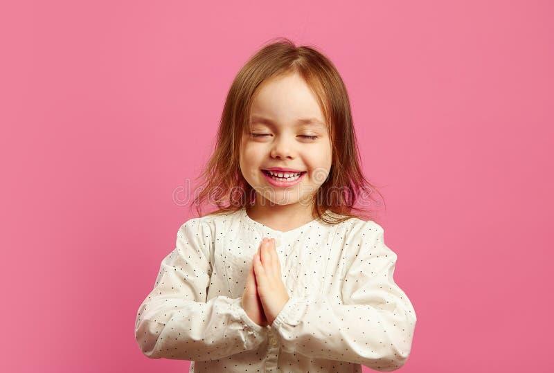 Το μικρό κορίτσι την δίπλωσε παραδίδει τους φοίνικες, έκλεισε τα μάτια, προσεύχεται ή κάνει μια επιθυμία, θέλει κάτι πάρα πολύ στοκ εικόνες