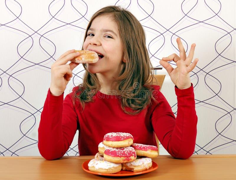 Το μικρό κορίτσι τρώει τα γλυκά donuts στοκ εικόνα
