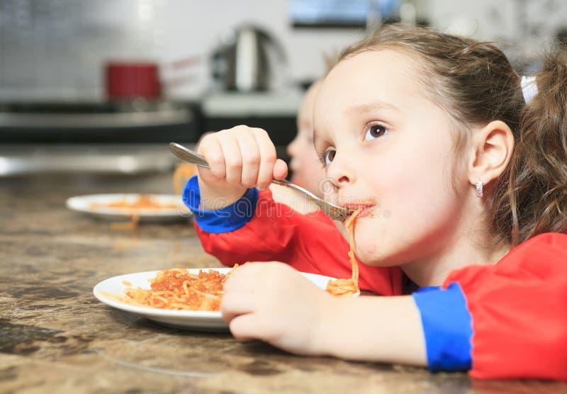 Το μικρό κορίτσι τρώει τα ζυμαρικά στον πίνακα κουζινών στοκ εικόνες με δικαίωμα ελεύθερης χρήσης