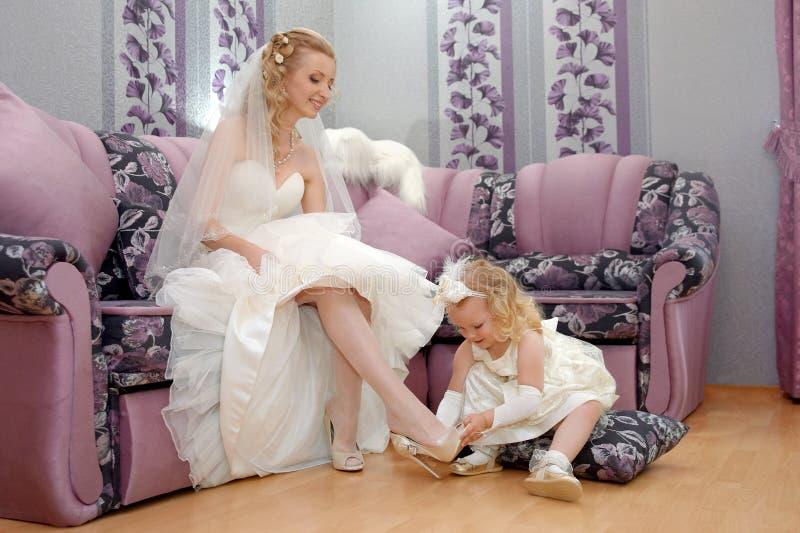 Το μικρό κορίτσι ` s mom παντρεύεται Η κόρη ντύνει mom το β στοκ φωτογραφία