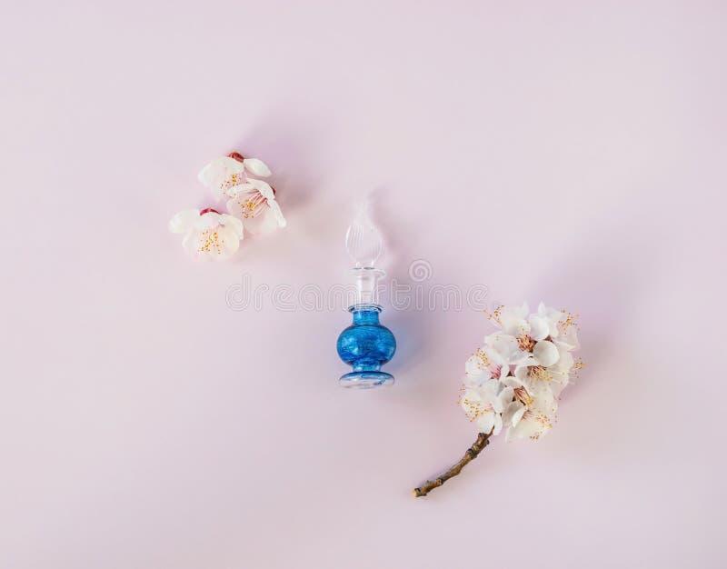 Το μικρό μπλε μπουκάλι αρώματος με τα λουλούδια από πάνω επίπεδα βάζει στοκ εικόνες