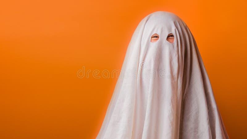 Το μικρό παιδί έντυσε σε ένα κοστούμι φαντασμάτων για αποκριές στο πορτοκαλί υπόβαθρο στοκ φωτογραφίες