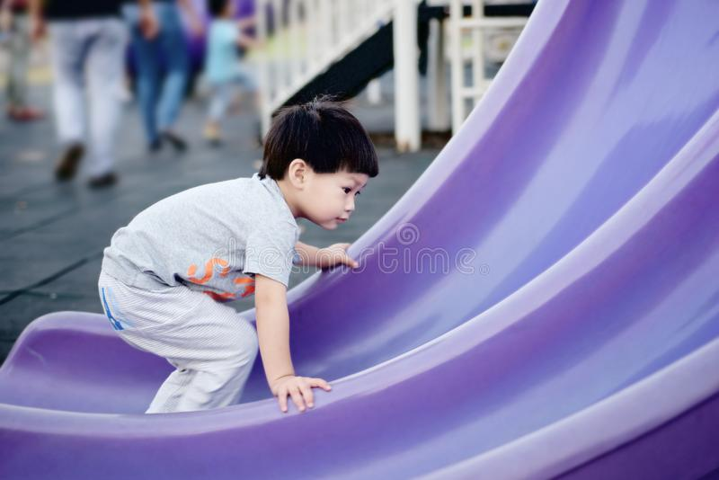 Το μικρό παιδί αναρριχείται επάνω στον αντίστροφο τρόπο φωτογραφικών διαφανειών στοκ εικόνες με δικαίωμα ελεύθερης χρήσης