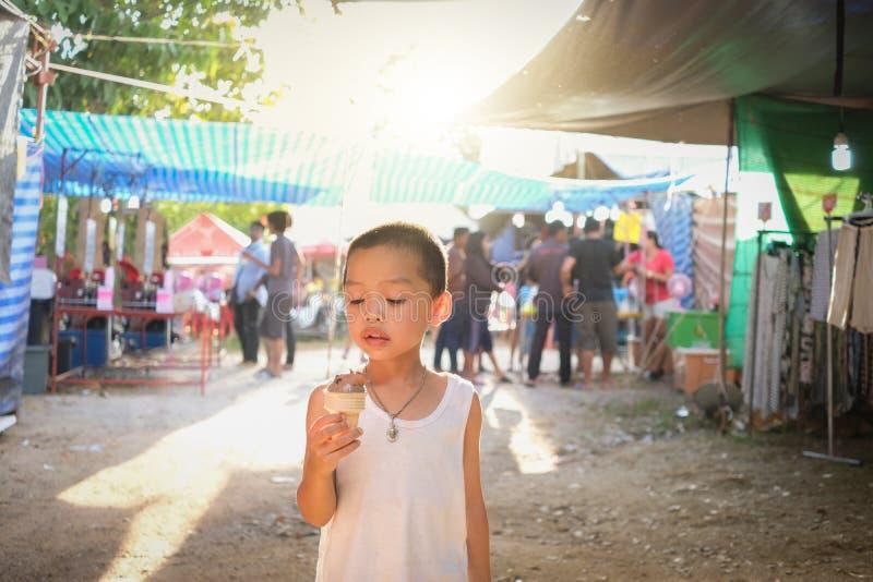 Το μικρό παιδί απολαμβάνει τον κώνο παγωτού σοκολάτας περπατώντας στην αγορά στοκ εικόνα