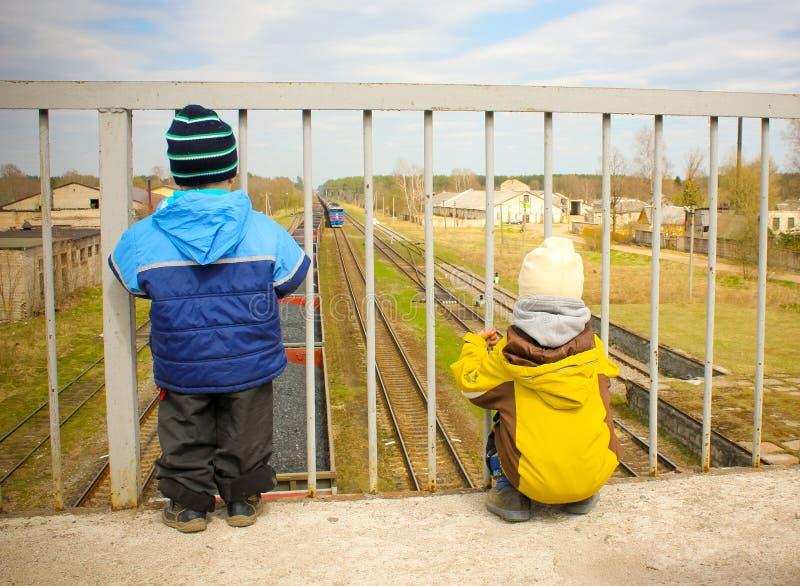 Το μικρό παιδί δύο εξετάζει το πλησιάζοντας τραίνο από τη γέφυρα για πεζούς στοκ φωτογραφία