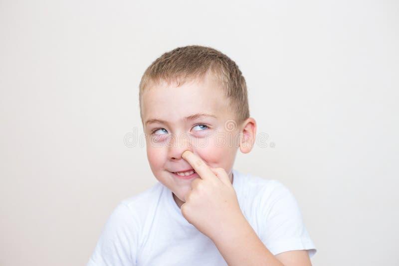 Το μικρό παιδί επιλέγει τη μύτη του σε ένα άσπρο υπόβαθρο στοκ φωτογραφία με δικαίωμα ελεύθερης χρήσης